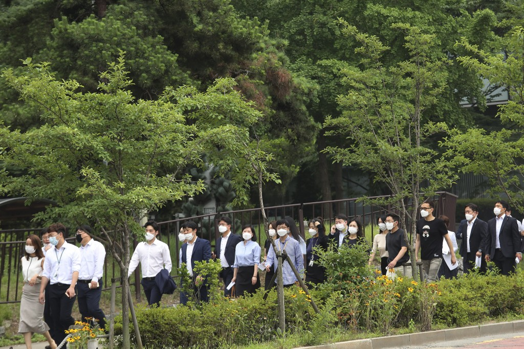 People wearing face masks to help protect against the spread of the new coronavirus cross a road in Seoul, Monday, June 29, 2020. (AP Photo/Ahn Young-...