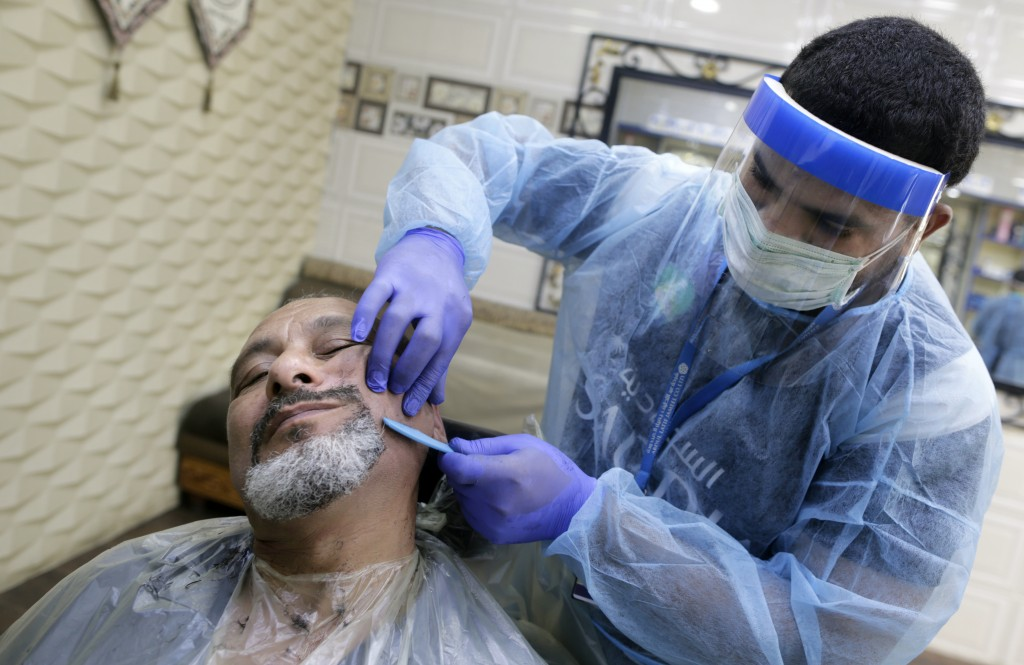A barber wears a protective face shield and gloves to help curb the spread of the coronavirus, as he shaves the beard of a customer at a local barber ...