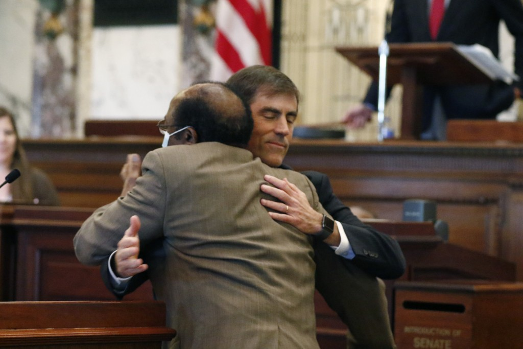 Sen. Briggs Hopson, R-Vicksburg, is hugged by Sen. Albert Butler, back to camera, D-Port Gibson, after the Senate voted to change the state flag Sunda...