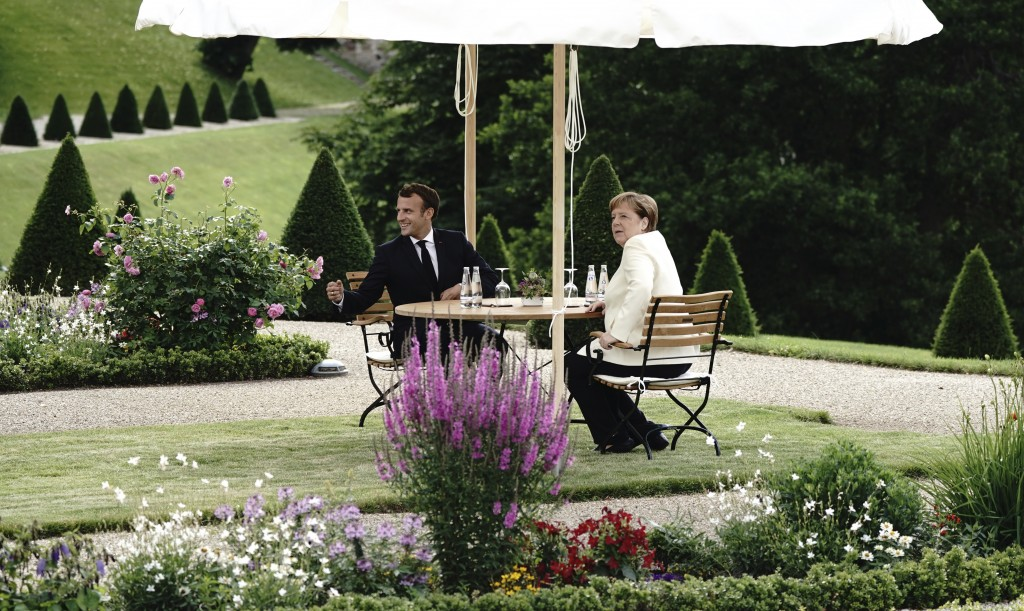 German Chancellor Angela Merkel and French President Emmanuel Macron pose during a meeting at Meseberg Castle, the German government's guest house in ...