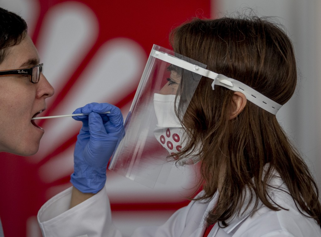 For demonstration purposes, an employee of the Centogene company takes a throat swab from a colleague at the airport in Frankfurt, Germany, Monday, Ju...