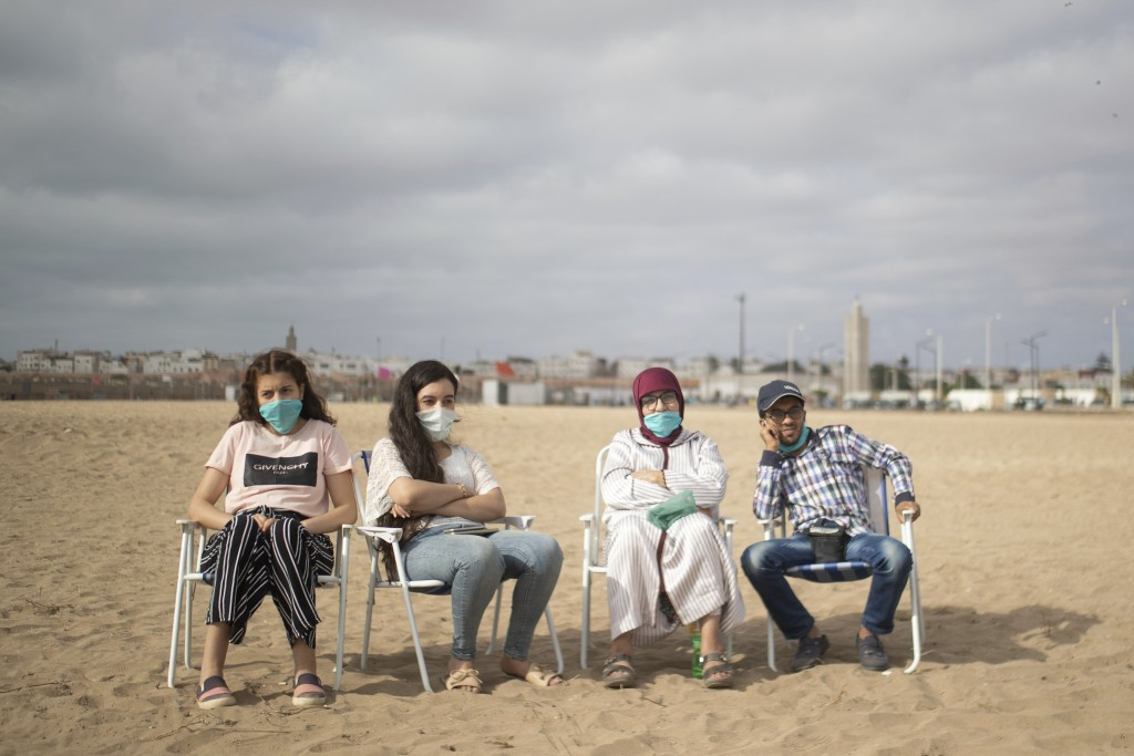 A family wears face masks to prevent the spread of Coronavirus while enjoying their time at a reopened beach in Sale, Morocco, Friday, June 26, 2020. ...