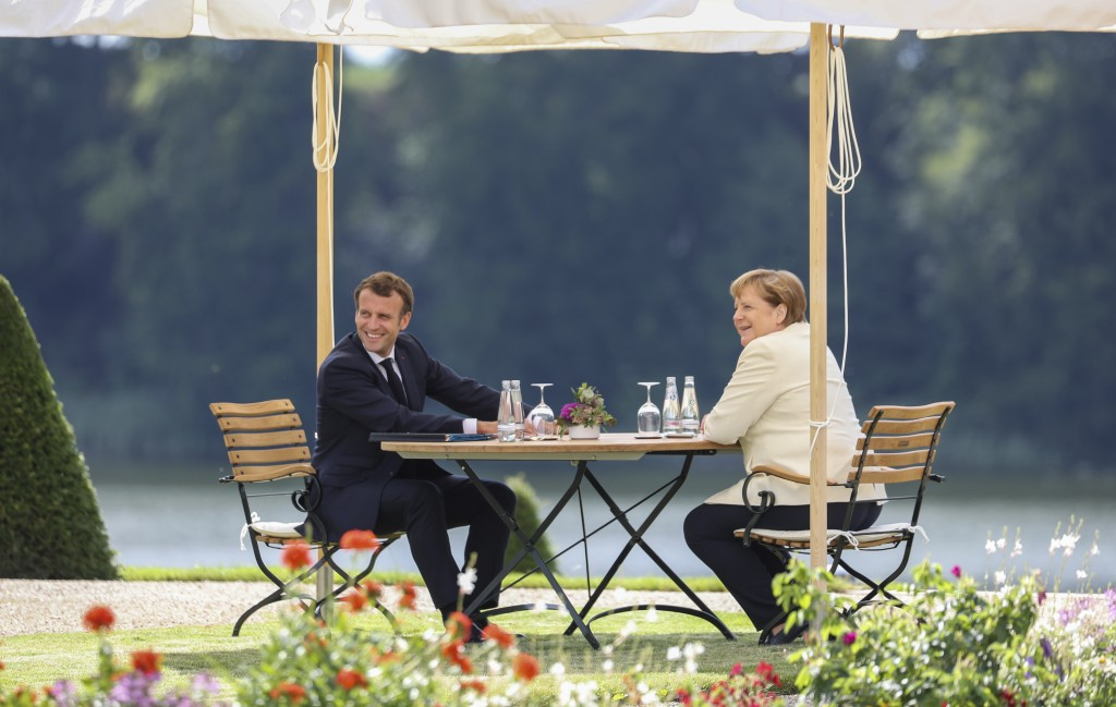 German Chancellor Angela Merkel and French President Emmanuel Macron, left, talk during a bilateral meeting at the German government's guest house Mes...