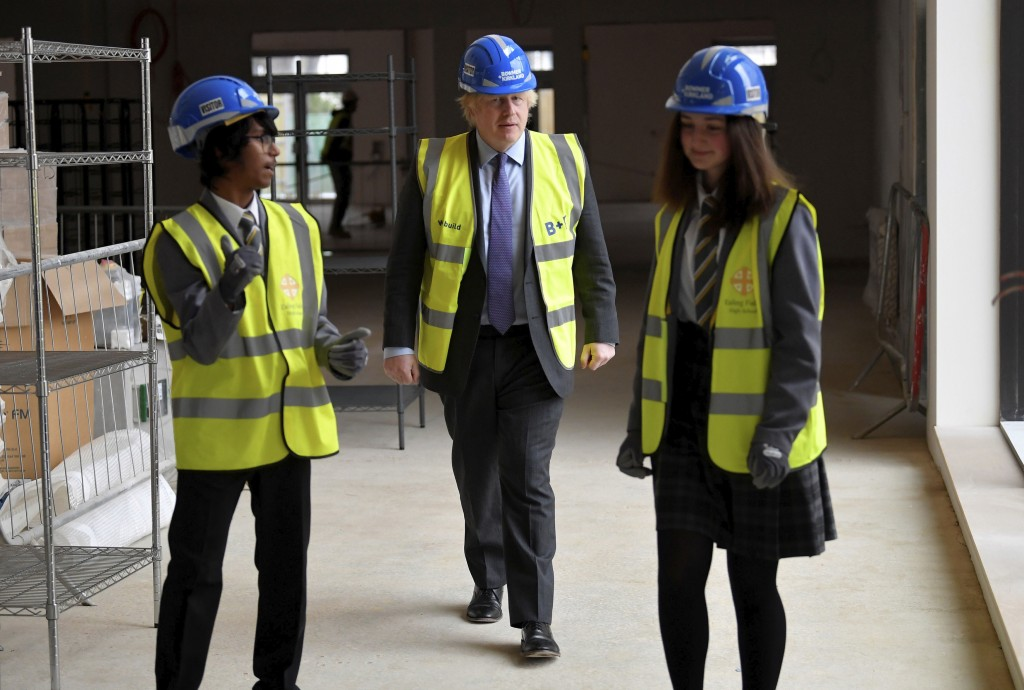 Britain's Prime Minister Boris Johnson talks with year 10 pupils Vedant Jitesh and Eryn Davies during a visit to the construction site of Ealing Field...