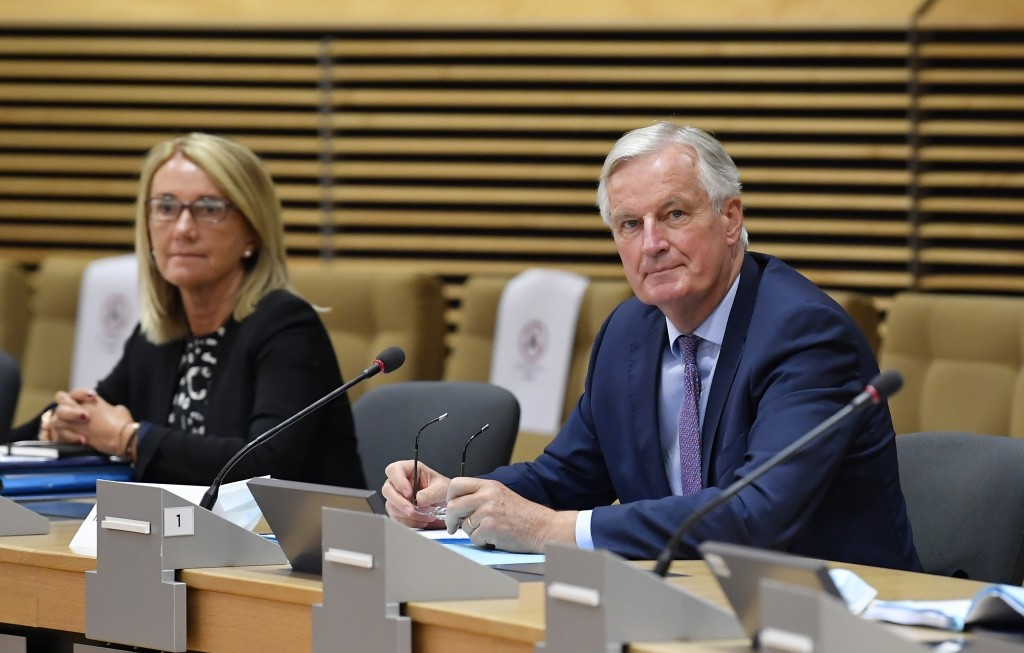 European Union's Brexit negotiator Michel Barnier, right, waits for the start of a meeting on further Brexit negotiations at EU headquarters in Brusse...