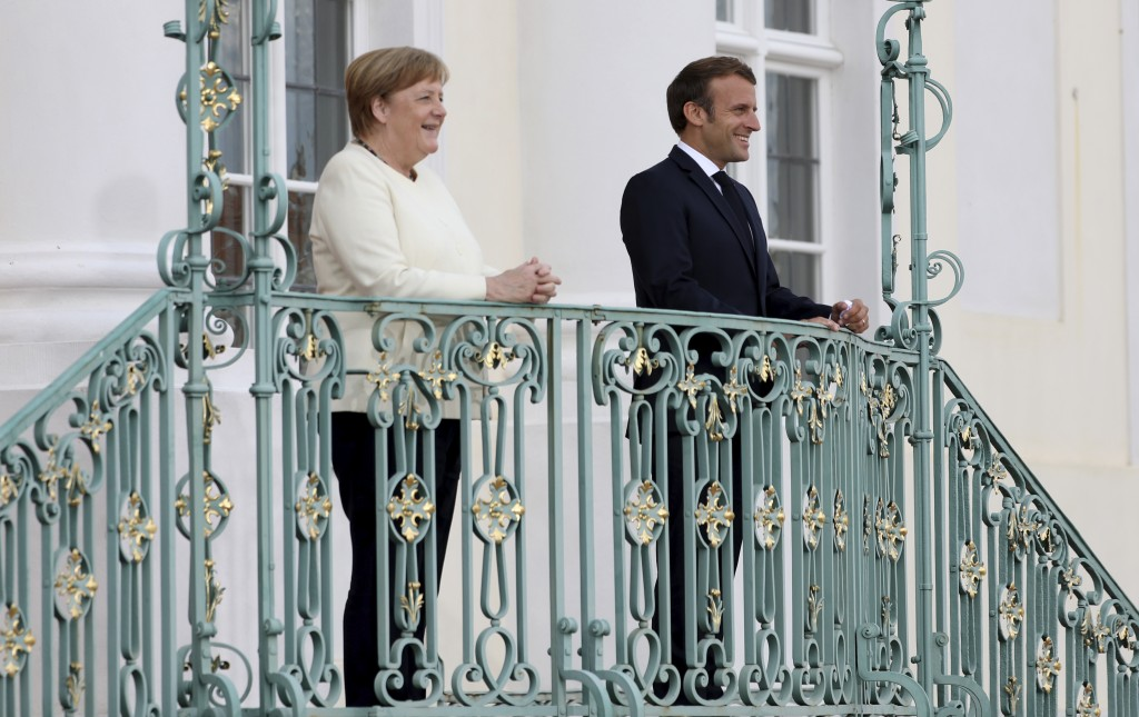 German Chancellor Angela Merkel and French President Emmanuel Macron, right, smile at the German government's guest house Meseberg Castle in Gransee n...