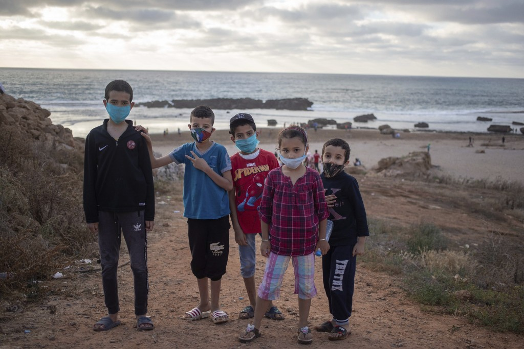 Boys wearing face masks to prevent the spread of Coronavirus pose for a portrait as they spend time at a reopened beach for the first time since lockd...