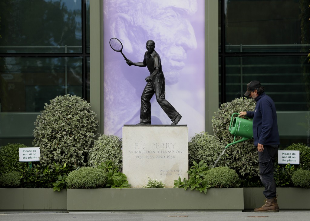 A gardener waters the plants alongside a statue of former Wimbledon Champion Fred Perry at the All England Lawn Tennis Club in Wimbledon in London, Mo...
