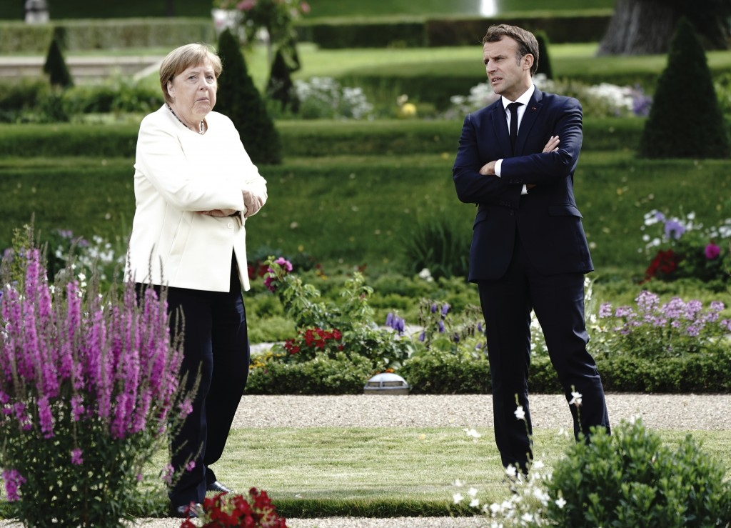 French President Emmanuel Macron talks to German Chancellor Angela Merkel during a meeting at Meseberg Castle, the German government's guest house in ...