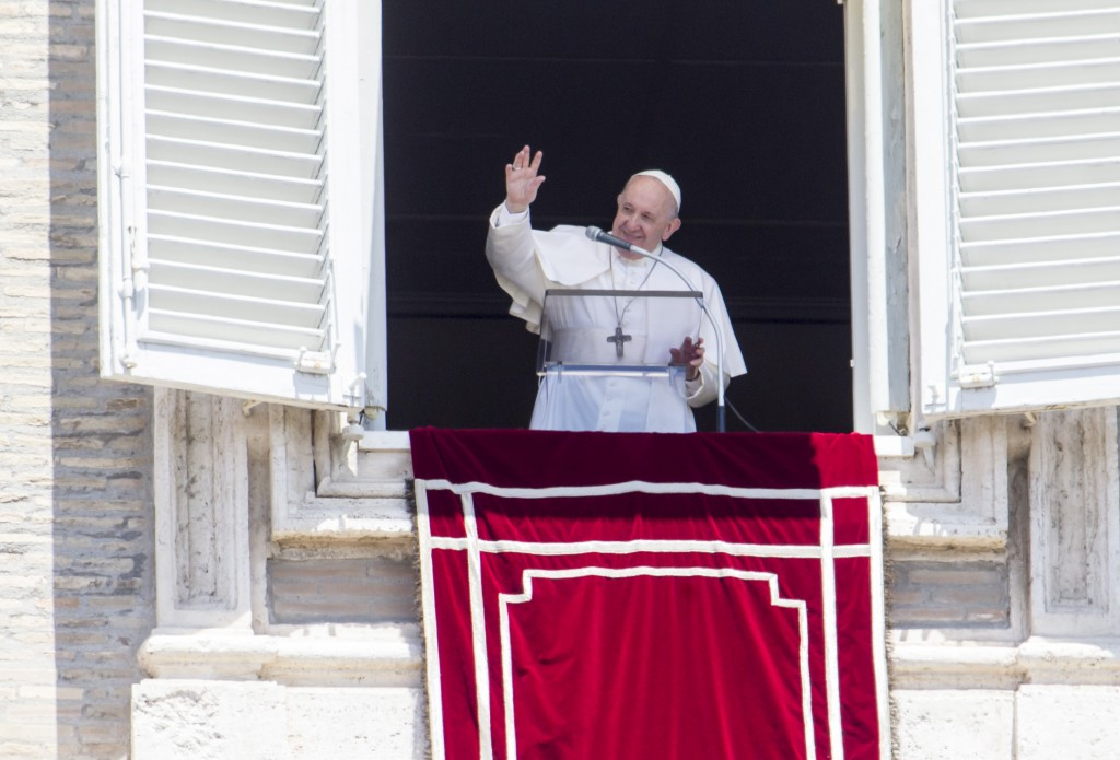 Pope Francis waves to the faithful at the end of the Angelus prayer from his studio window overlooking St. Peter's Square, after celebrating a Mass fo...