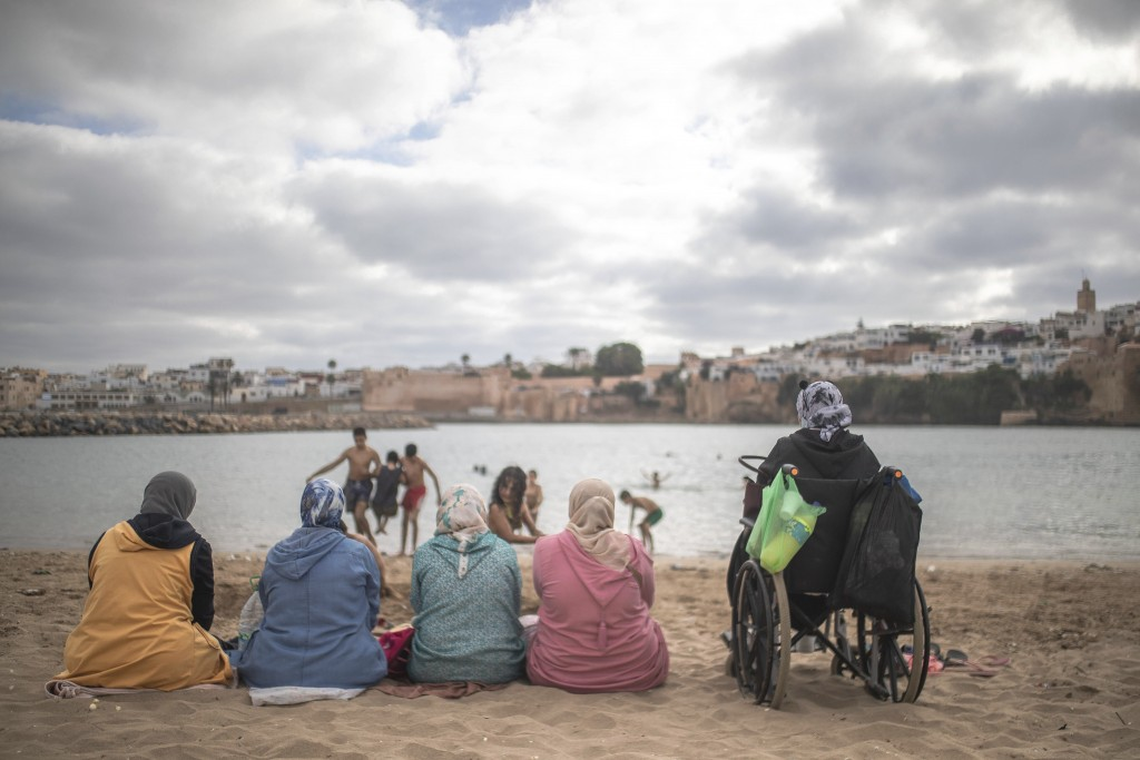 Women watch as their kids swim at a reopened beach after lockdown measures were lifted in Sale, Morocco, Friday, June 26, 2020. (AP Photo/Mosa'ab Elsh...