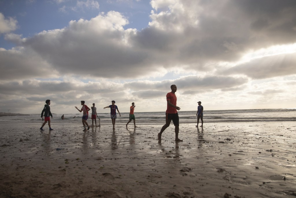 Youths play as the sun sets on a reopened beach after lockdown measures were lifted in Rabat, Morocco, Friday, June 26, 2020. (AP Photo/Mosa'ab Elsham...