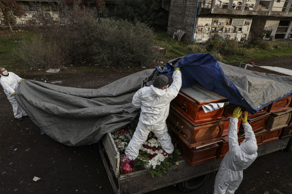 Workers collect and stack the coffins of people that have been recently cremated amid the new coronavirus pandemic, at the La Recoleta cemetery in San...