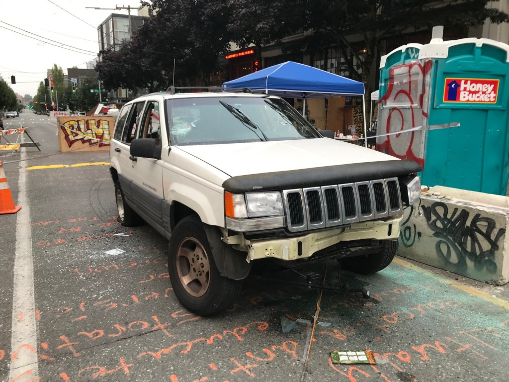 A car sits in the Capitol Hill Organized Protest zone following a shooting in Seattle early Monday, June 29, 2020. At least one man was killed and ano...