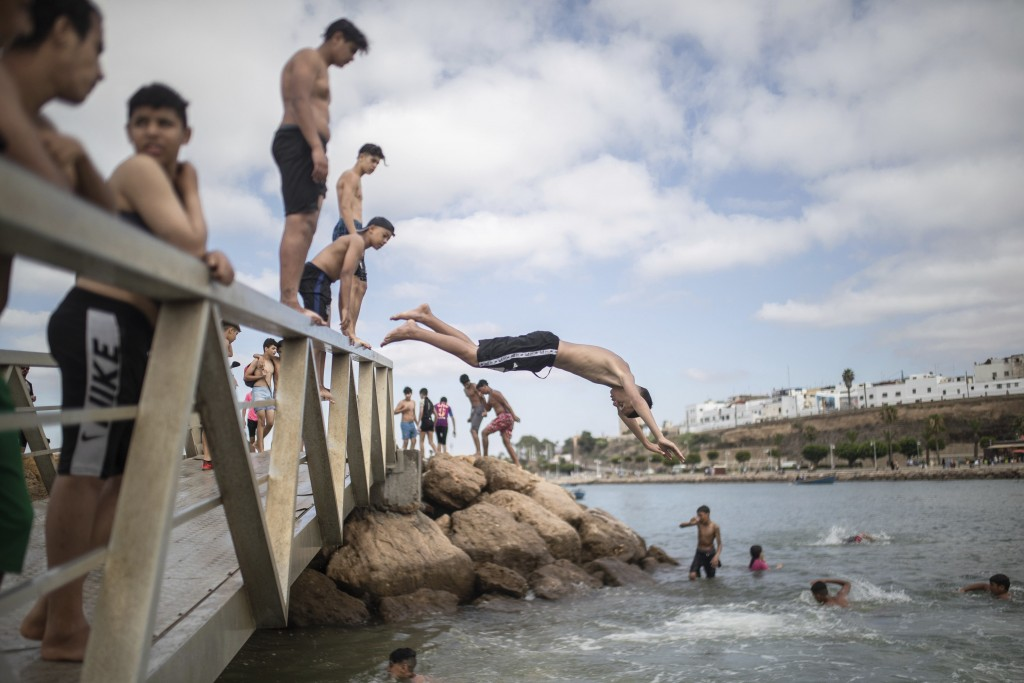 Boys jump into a river to cool down after lockdown measures were lifted in Rabat, Morocco on Friday, June 26, 2020. Moroccans are re-experiencing a ta...