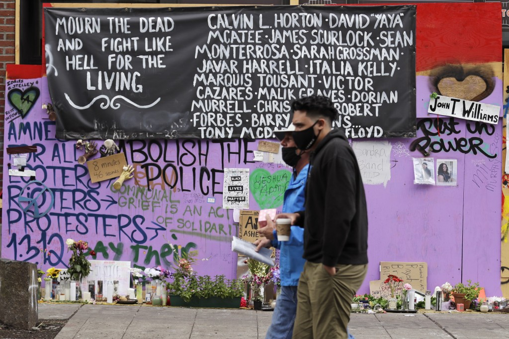 Two people walk past a memorial Sunday, June 28, 2020, in Seattle, for people of color believed to have died in police custody, where several streets ...