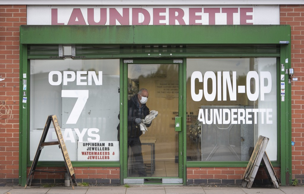 A man cleans the windows of a launderette in Leicester, England, Monday June 29, 2020. The central England city of Leicester is waiting to find out if...