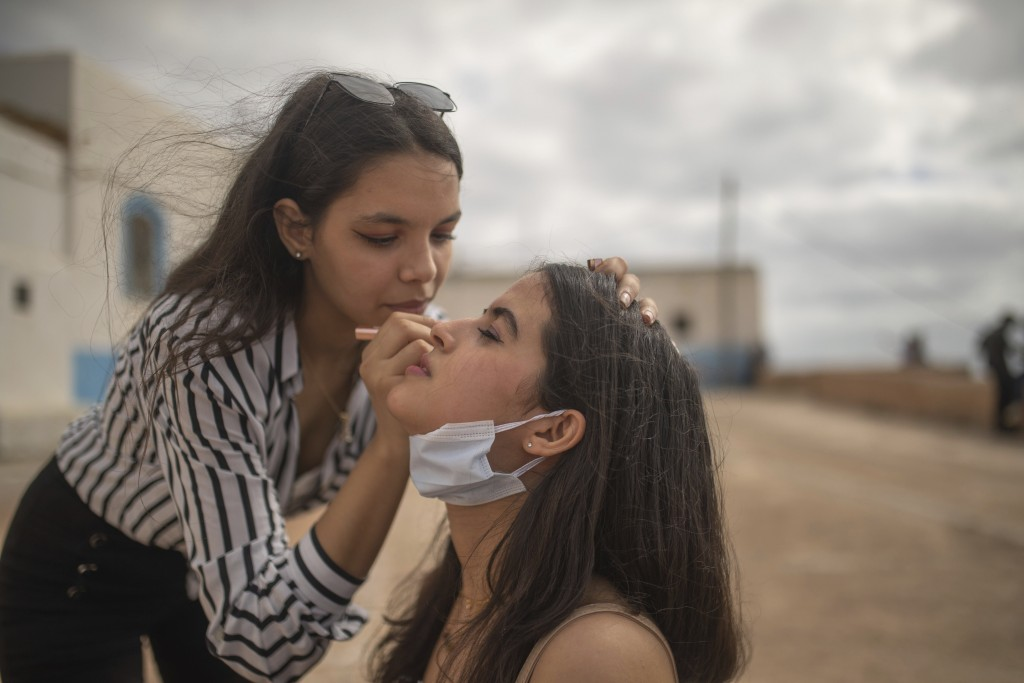 Yasmin, left, applies makeup for her friend, Mariam, as they spend time outdoors for the first time since lockdown measures were lifted, in Rabat, Mor...