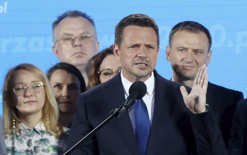 A top candidate in Poland's presidential election, Warsaw Mayor Rafal Trzaskowski, front, reacts to the exit poll after voting closed, in Warsaw, Pola...