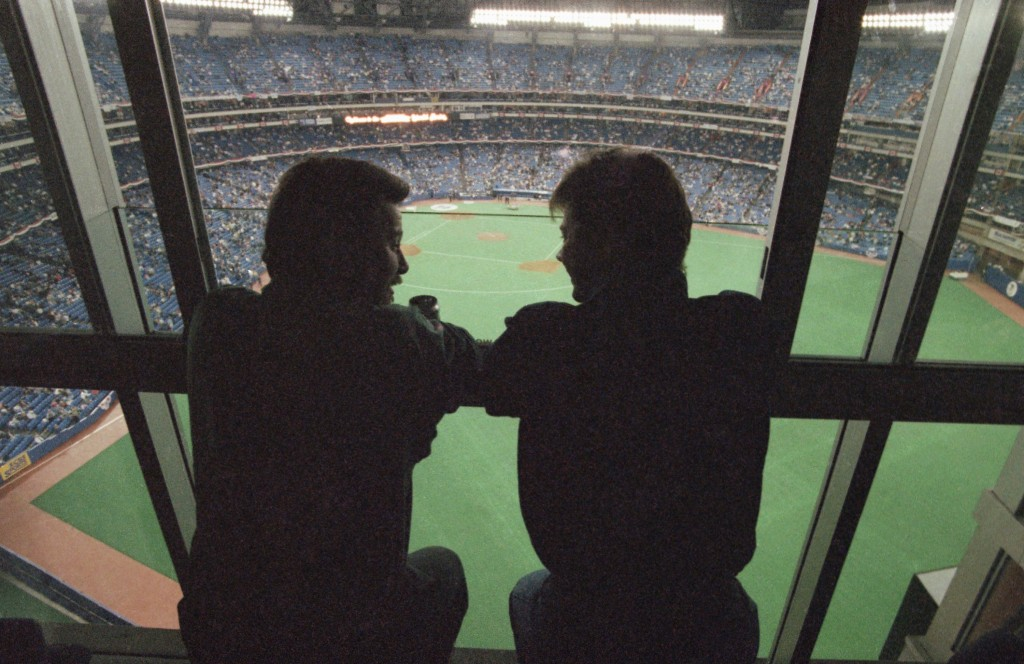 FILE - In this Oct. 22, 1992, file photo, spectators look out at the field of the SkyDome in Toronto, from a window of the SkyDome Hotel before Game 5...