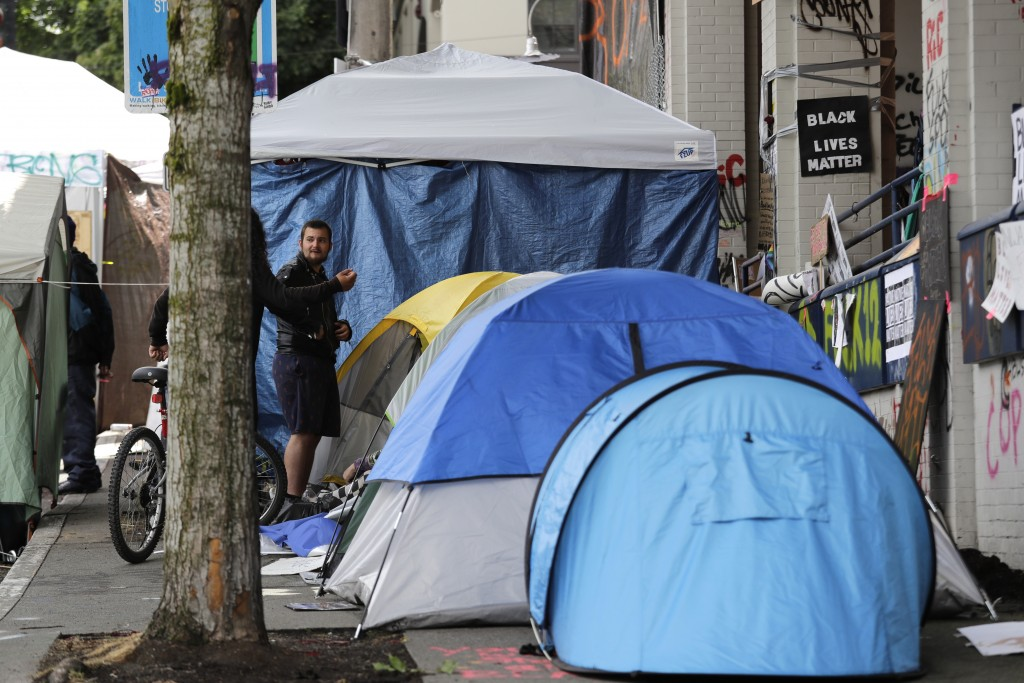 Tents line a sidewalk adjacent to a closed Seattle police precinct Sunday morning, June 28, 2020, in Seattle, where several streets are blocked off in...