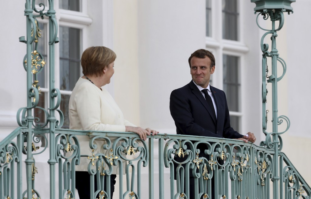 German Chancellor Angela Merkel and French President Emmanuel Macron, right, look to each other at the German government's guest house Meseberg Castle...