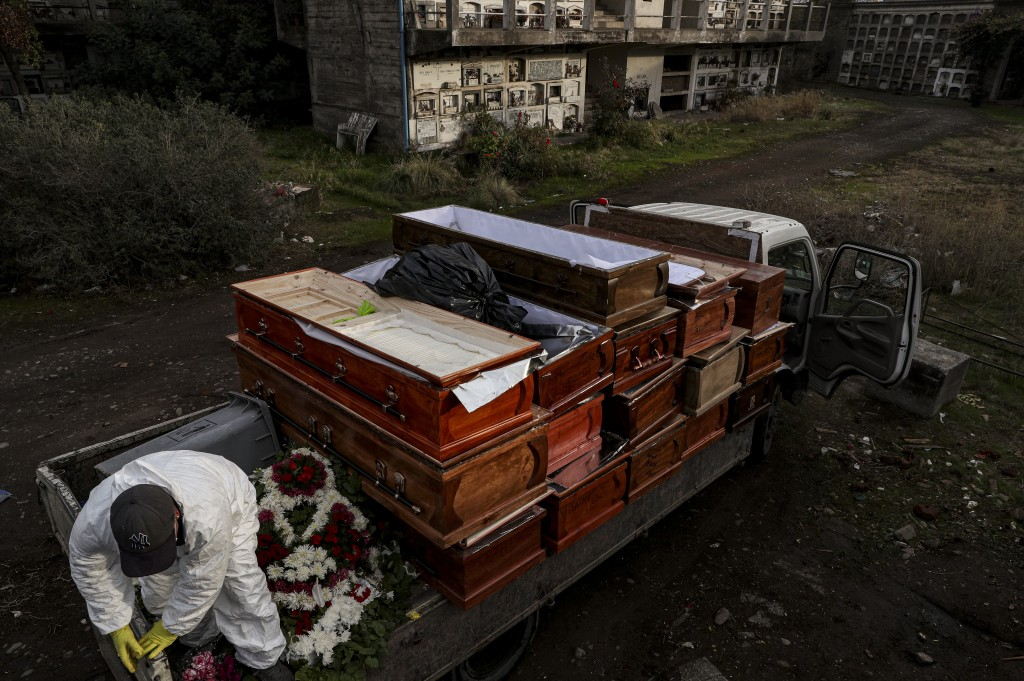 Workers collect the coffins of people that have been recently cremated amid the new coronavirus pandemic, at the La Recoleta cemetery in Santiago, Chi...