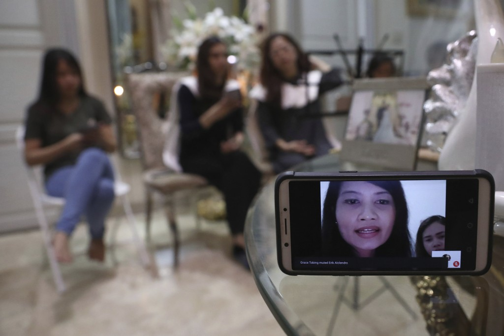 A relative of Dr. Michael Robert Marampe is seen through a mobile phone screen as she attends an online memorial service to mark the 40th day since Ma...