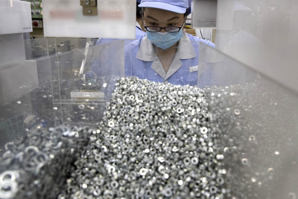 In this Wednesday, May 13, 2020 photo, a worker at SMC China, a Japanese joint venture pneumatic engineering company, assembles products at a factory ...
