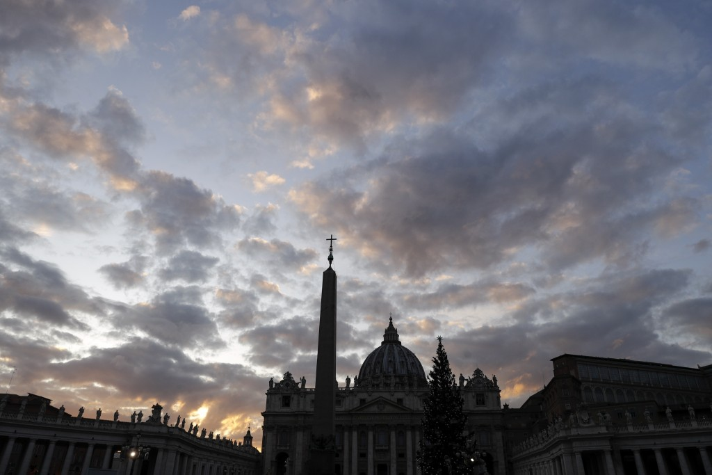 FILE - In this Thursday, Dec. 5, 2019 file photo, the sun sets over St. Peter's Basilica, at the Vatican. Vatican prosecutors have ordered the seizure...
