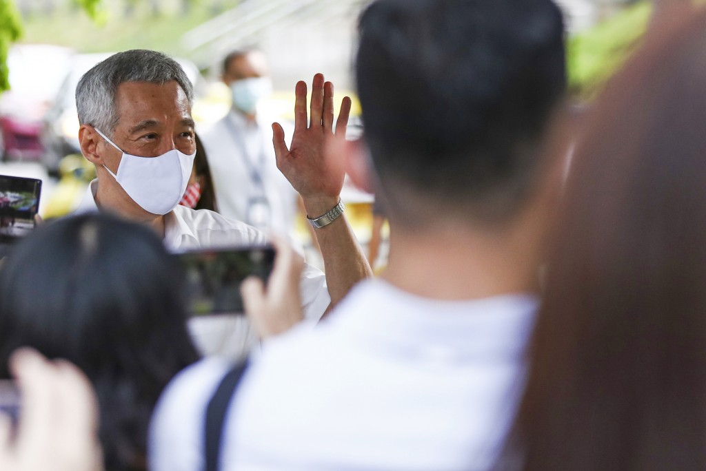 People's Action Party Secretary-General and Singaporean Prime Minister Lee Hsien Loong, left, arrives at a nomination center with his team to submit t...
