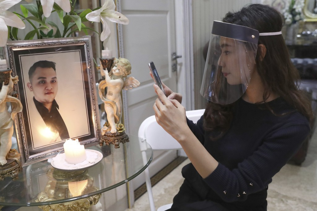 Tri Novia Septiani takes a photo of a portrait of her fiance Dr. Michael Robert Marampe during an online memorial service to mark the 40th day since M...