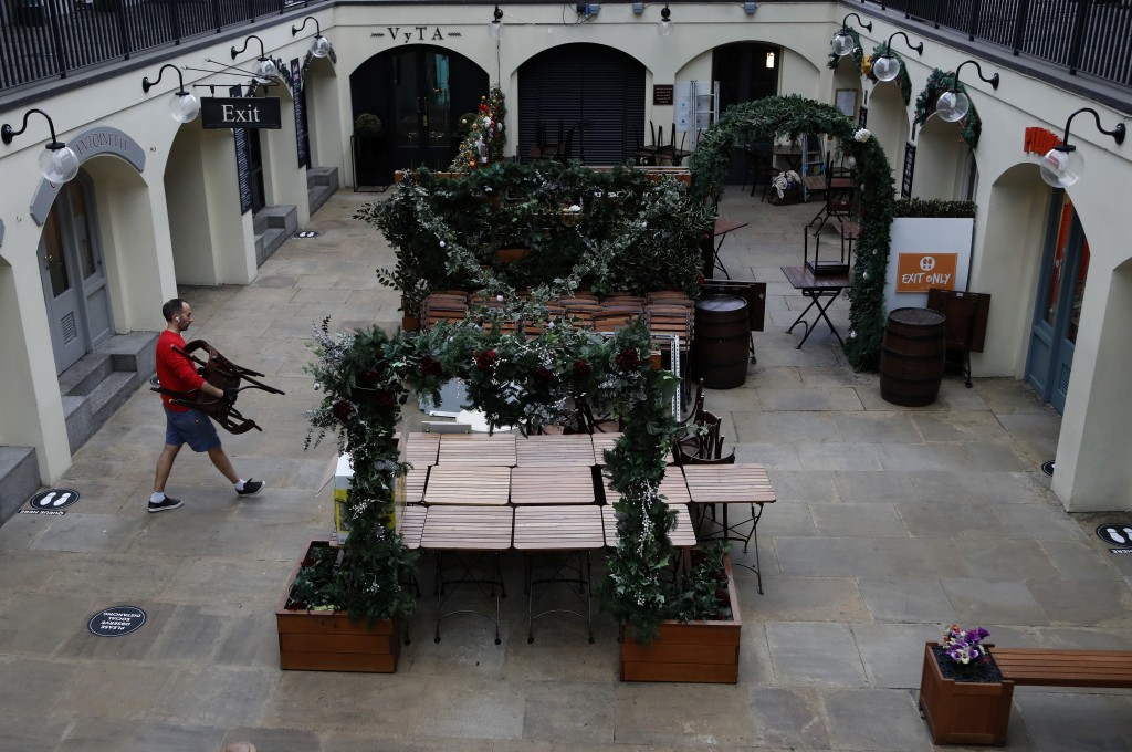 An owner of a restaurant starts preparing the outdoor seating for the reopening at Covent Garden in London, Tuesday, June 30, 2020. Tuesday marked 100...