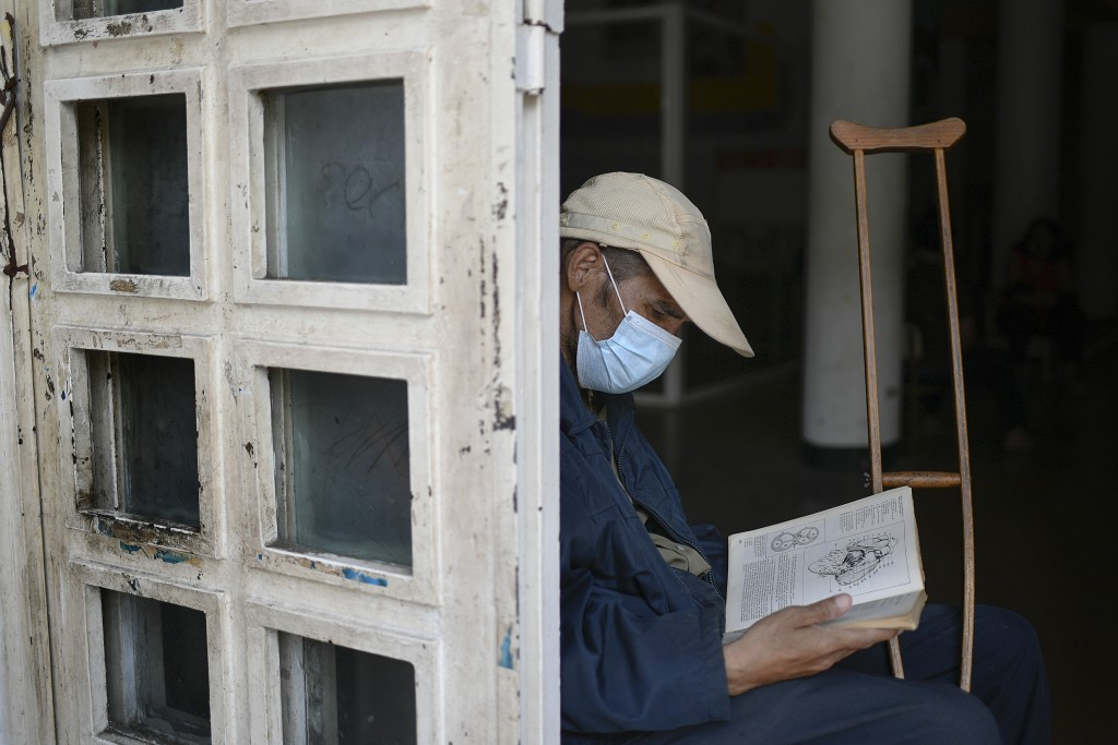 An elderly man who uses a crutch due to having lost half his leg reads a book at a cultural center in La Pastora neighborhood of Caracas, Venezuela, M...
