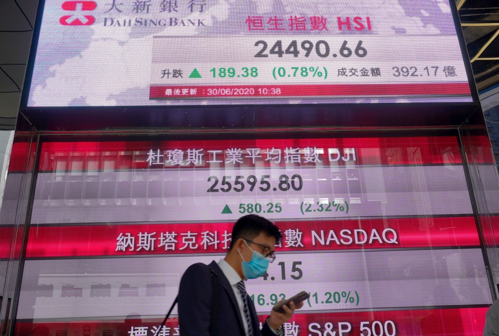 A man wearing a face mask walks past a bank's electronic board showing the Hong Kong share index at Hong Kong Stock Exchange Tuesday, June 30, 2020. A...