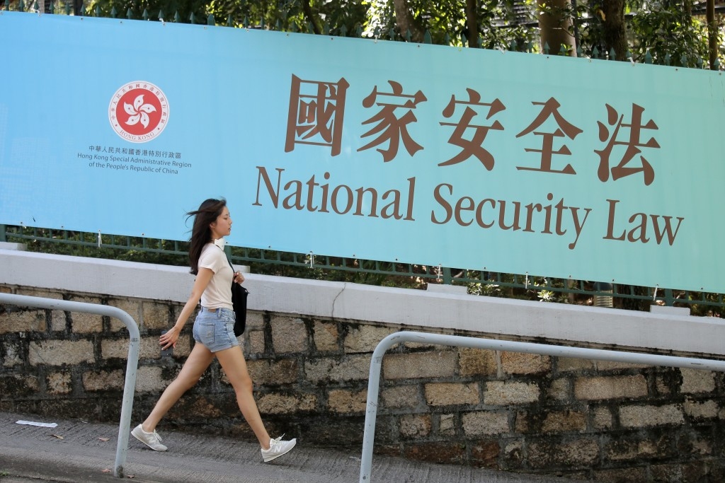 A woman walks past a promotional banner of the national security law for Hong Kong, in Hong Kong, Tuesday, June 30, 2020. China has approved a content...