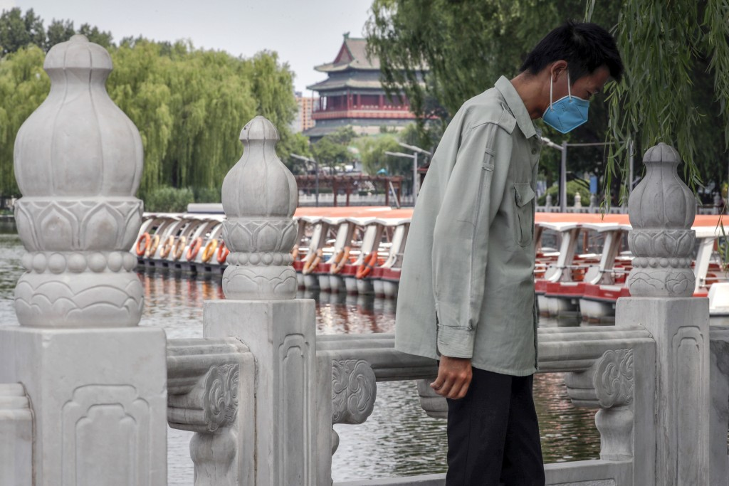 A man wearing a protective face mask to help curb the spread of the coronavirus stands against a roll of boats parked on the barricaded Houhai Lake, a...