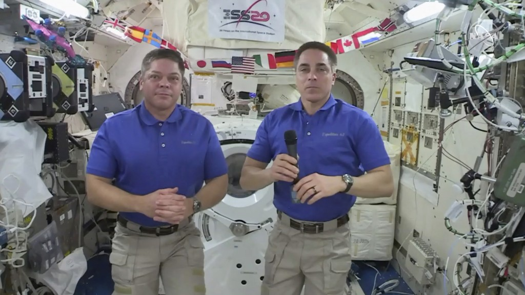In this image taken from NASA video, NASA astronaut Chris Cassidy, right answers a question as fellow astronaut Robert L. Behnken listens during an in...