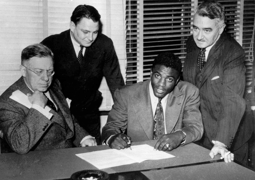 FILE - In this Oct. 23, 1945, file photo, Jackie Robinson, first Negro player in the major leagues, signs with the Montreal Royals in Montreal. From l...