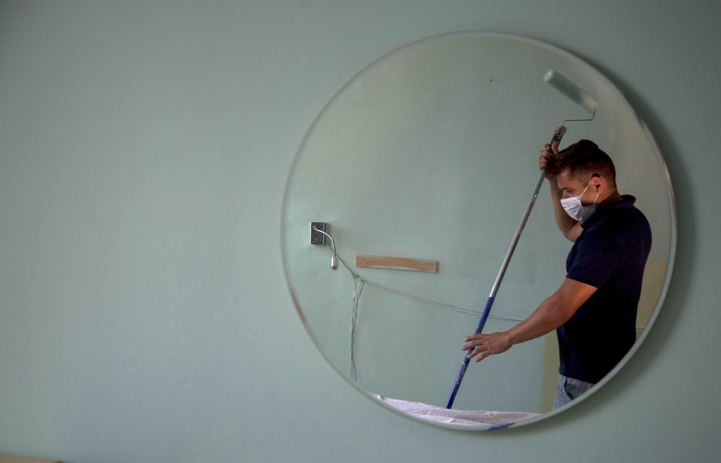 Hotel maintenance worker Elgis Moreno is reflected on a mirror as he paints a room at the Capri Hotel, during a lockdown affecting tourism to curb the...
