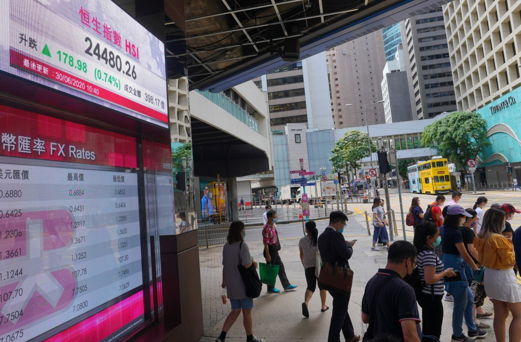 People wearing a face mask walks past a bank's electronic board showing the Hong Kong share index at Hong Kong Stock Exchange Tuesday, June 30, 2020. ...