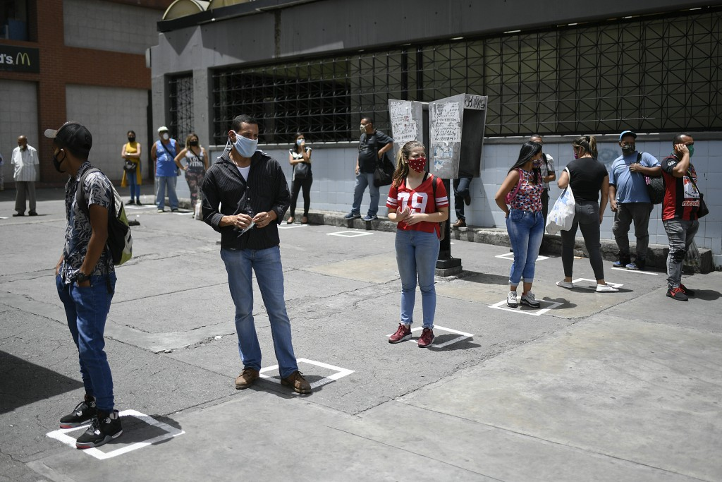 Commuters stand on visual cues to encourage social distancing, as a precaution amid the spread of the new coronavirus, at a bus stop in downtown Carac...