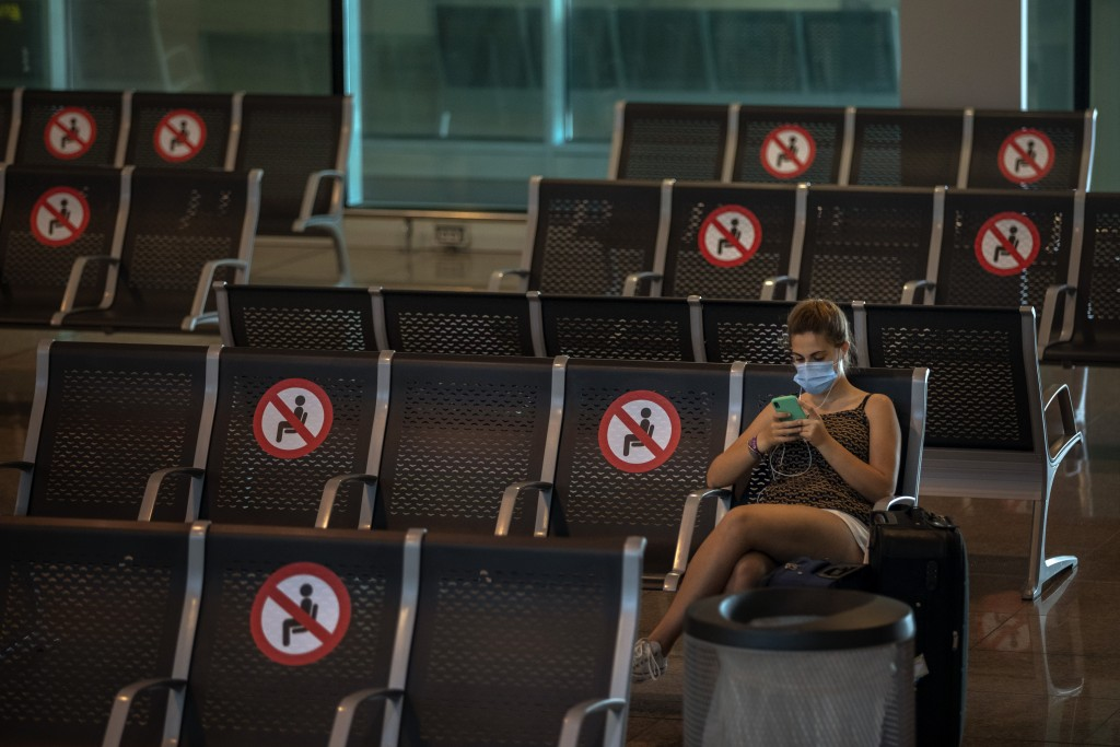 A passenger sits at Barcelona airport in Barcelona, Spain, Tuesday, June 30, 2020. The European Union on Tuesday is announcing a list of nations whose...