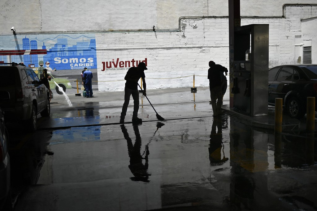 A city worker sweeps disinfectant on the ground as a preventive measure amid the spread of the new coronavirus at a state-run gas station in Caracas, ...