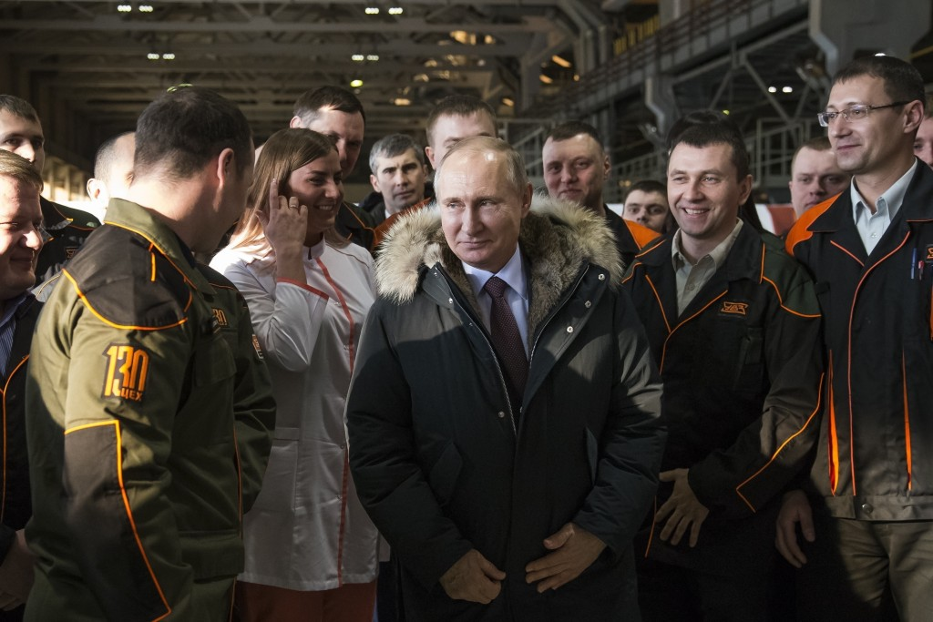 FILE - In this March 6, 2018, file photo, Russian President Vladimir Putin listens to employees of Uralvagonzavod factory in Nizhny Tagil, Russia. In ...