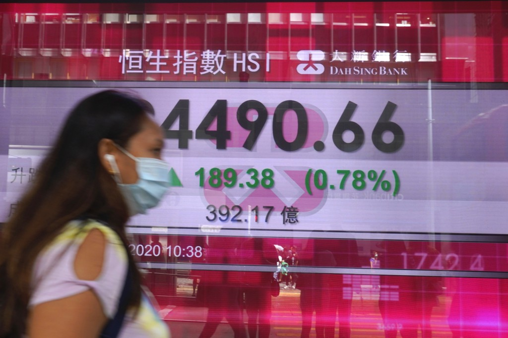 A woman wearing a face mask walks past a bank's electronic board showing the Hong Kong share index at Hong Kong Stock Exchange Tuesday, June 30, 2020....