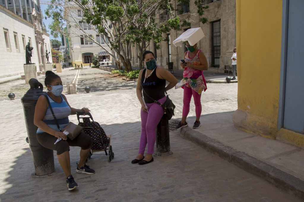 Women wearing masks to curb the spread of the new coronavirus chat on a corner in Old Havana, one using a piece of styrofoam to shade herself, in Hava...