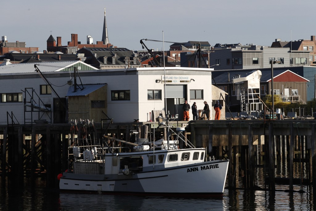 FILE - This March 25, 2020, file photo shows workers gathered outside the Portland Fish Exchange after unloading fish in Portland, Maine. On this day ...