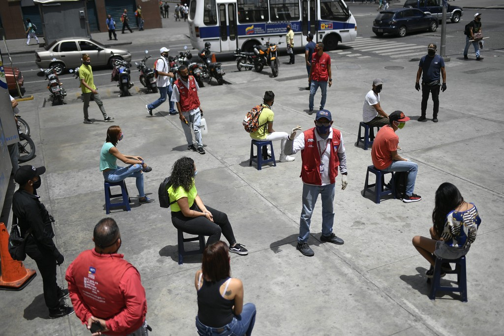 A worker from the Transportation Ministry explains proper mask usage to non-compliant pedestrians on a corner of downtown Caracas, Venezuela, Monday, ...