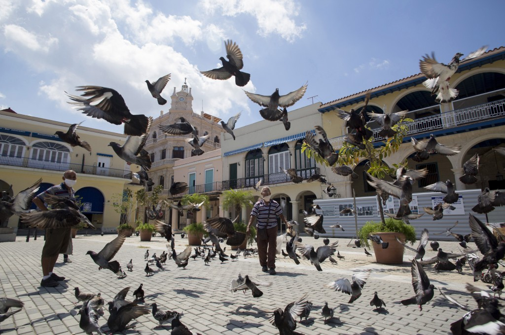 Pigeons take flight in an empty Plaza Vieja in Havana, Cuba, Tuesday, June 23, 2020. Nearly three months of a near-total shutdown of commerce, transpo...
